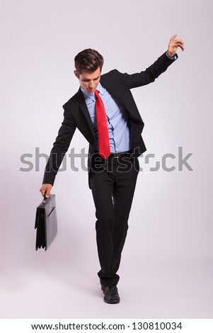 Business man holding a briefcase balancing and walking forward on an imaginary rope on gray background - stock photo