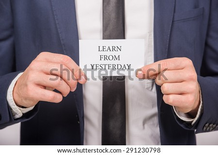 Business man holding a card with message text written on it. Close-up. - stock photo