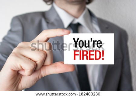 Business man holding a card with you're fired text - stock photo