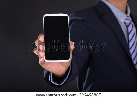 Business man holding a cell phone, close-up , Black background.
