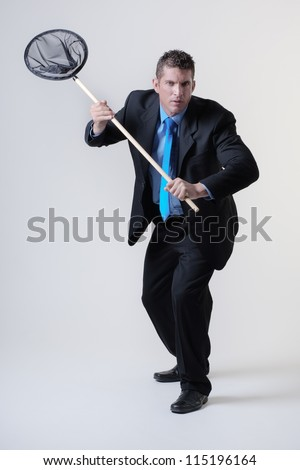 business man holding a fishing net trying to find and catch new business - stock photo
