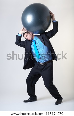 business man holding a gym ball above his head