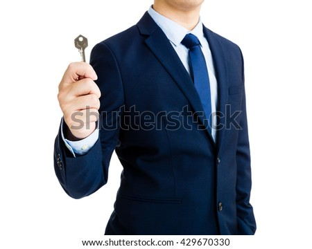 Business man holding a home key