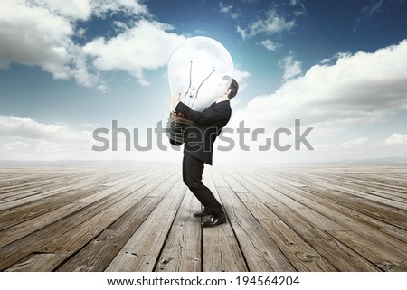 business man holding a huge bulb lamp - stock photo