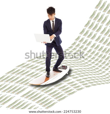 business man holding a laptop and surfing on the money wave .  - stock photo