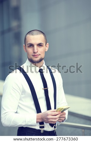 Business man holding a money hundred dollar banknotes. Businessman on blurring background office building work. Man receiving money, US dollars. Income from investment - a highly profitable business. - stock photo