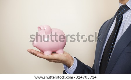 Business man holding a piggy banck - stock photo