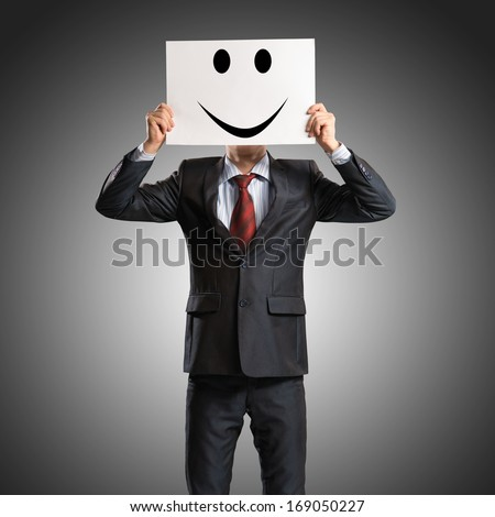 business man holding a poster with a painted face on it instead of a face, the concept of duplicity in business