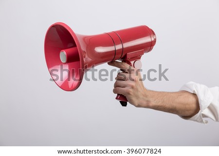 Business man holding a red loudspeaker against white background