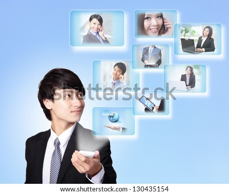 Business man holding a touch smart phone and surfing in the social network, isolated on blue background, asian model - stock photo
