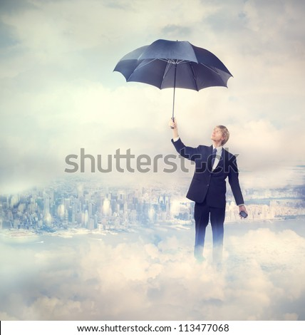 Business man holding an umbrella on the clouds - stock photo