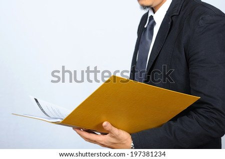 Business-man holding and checking work with yellow folder. - stock photo