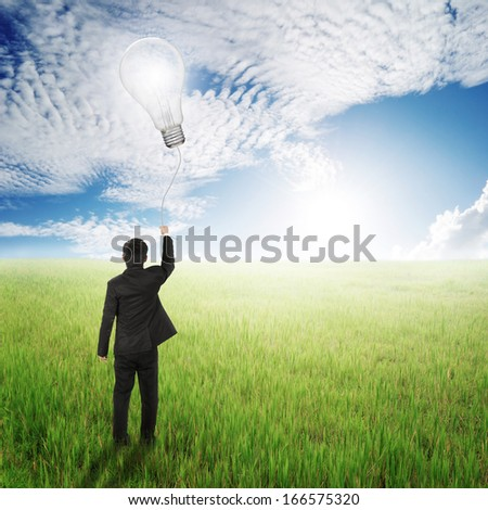 Business man holding bulb balloon in fields and sun sky  - stock photo
