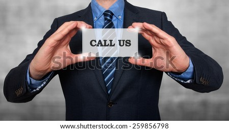 Business man holding Call Us card. Grey - Stock Photo - stock photo
