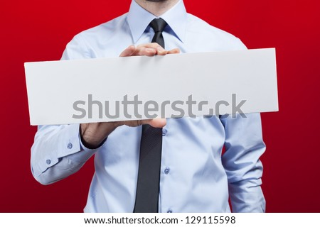 Business man holding card against red background. - stock photo