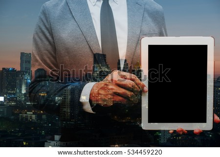 business man holding computer tablet double exposure with building