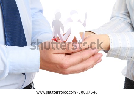 Business man holding cut out paper people - stock photo