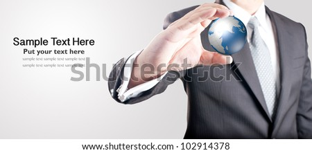 Business man holding digital globe with blank space for text on left - stock photo