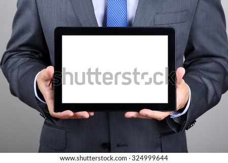 Business man holding digital tablet PC showing something on blank screen. Copyspace. - stock photo