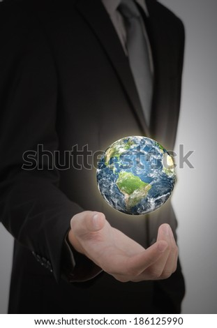 Business man holding earth in his hand (Elements of this image furnished by NASA) - stock photo
