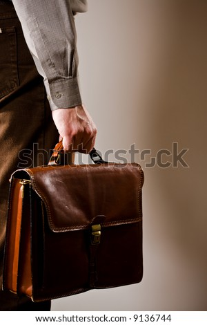 Business man holding elegant brown leather briefcase. - stock photo