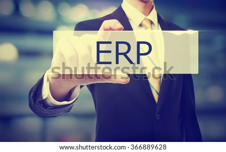 Business man holding ERP on blurred abstract background   - stock photo