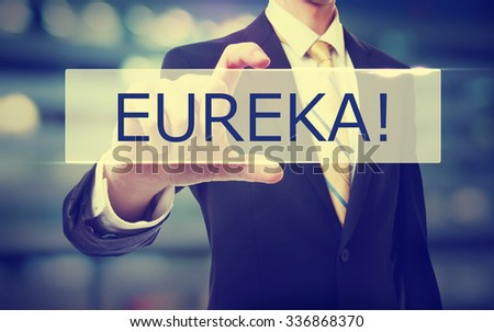 Business man holding Eureka on blurred abstract background   - stock photo