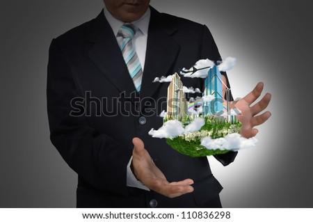 Business Man holding floating city on blue background - stock photo