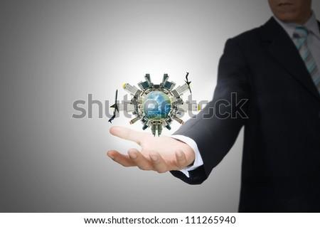 Business Man holding floating city on grey background - stock photo