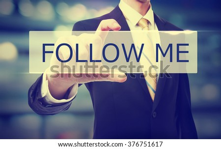 Business man holding Follow Me on blurred abstract background