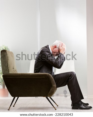 business man holding his head with his hands because of his negative feelings