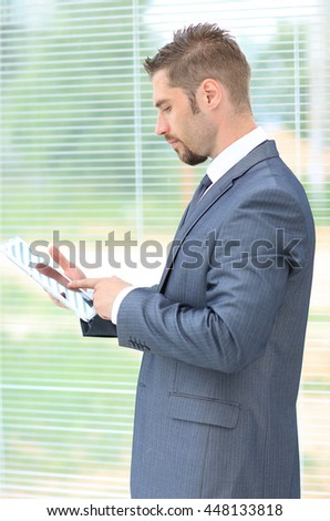 Business man holding his tablet and working against the window in an office - stock photo