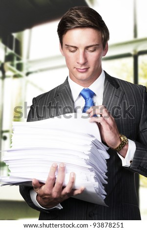 business man holding in his arms a lager pile of paper work - stock photo
