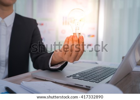 Business man holding light bulb - stock photo