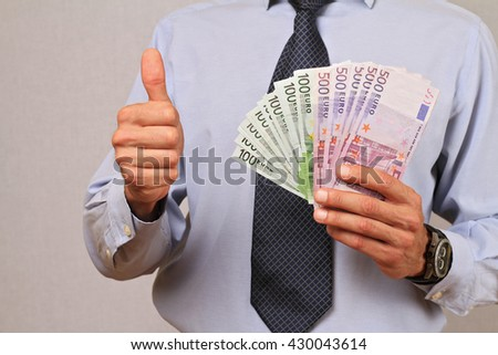 Business Man holding money and showing thumbs up. Success, investment, financial growth, profit, dividends concept