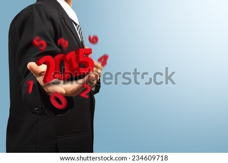 Business man holding 2015 new year - stock photo