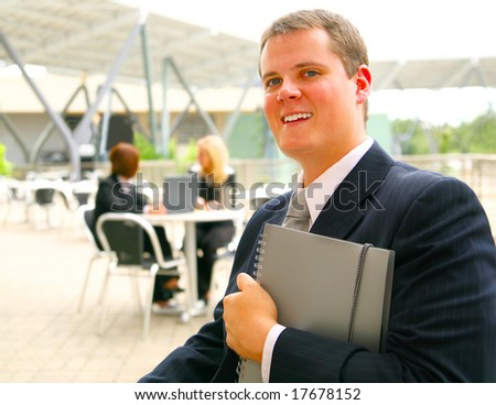 business man holding notebook with two of his associates sitting on the background
