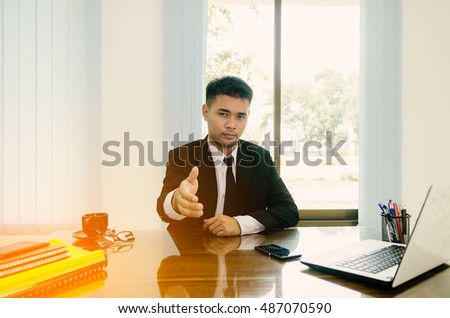 Business man holding out hand to close deal and welcome you, business partners concept