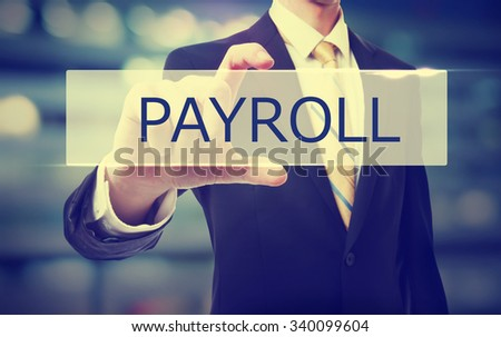 Business man holding Payroll on blurred abstract background   - stock photo
