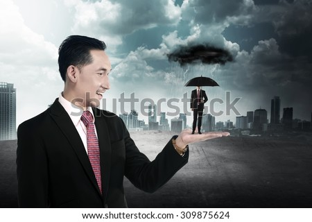 Business man holding small man using umbrella to protect himself from storm - stock photo