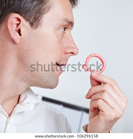 Business man holding speech balloon symbol near his mouth - stock photo