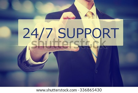 Business man holding 24/7 Support on blurred abstract background   - stock photo