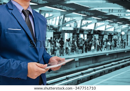 business man holding tablet in hand in event background