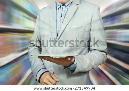 Business Man Holding Tablet in Supermarket outlet as Retail Wireless Technology.  Double exposure applied. - stock photo