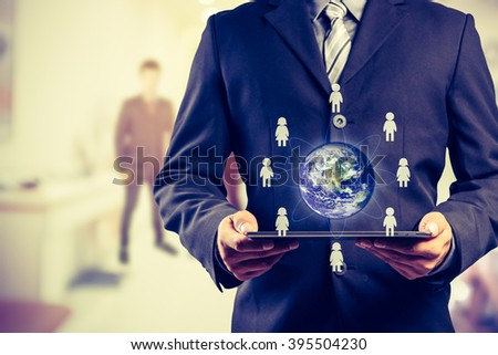 Business man holding tablet pc with businesspeople icons around the small world (Elements of this image furnished by NASA) - stock photo