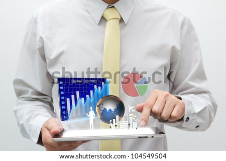 Business man holding tablet pc with graph, chart, pie, globe and building are flying off the screen - stock photo