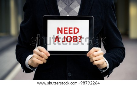 "Business man holding tablet pc with ""Need a job?"" text on screen. - stock photo"
