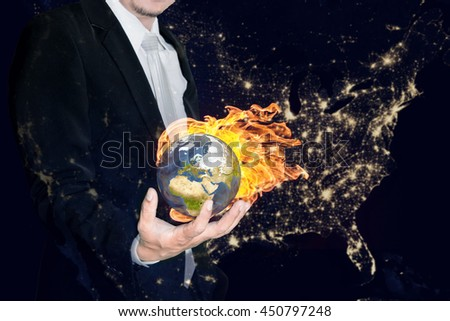 Business man holding the burning global earth in his hands against america city night light.Global warming and ecology concept. (Elements of this image furnished by NASA) - stock photo