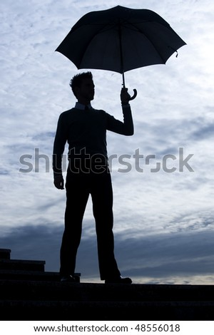 Business man holding umbrella against blue sky - stock photo