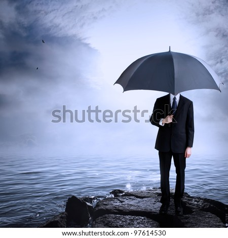 Business Man Holding Umbrella at the Coast After or Before a Storm - stock photo